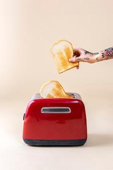 赤いトースターから飛び出すパンを持っている手