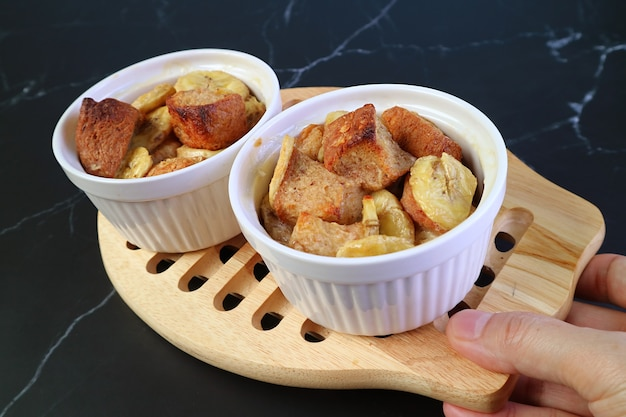 Hand holding a breadboard of fresh baked delectable banana bread pudding bowls