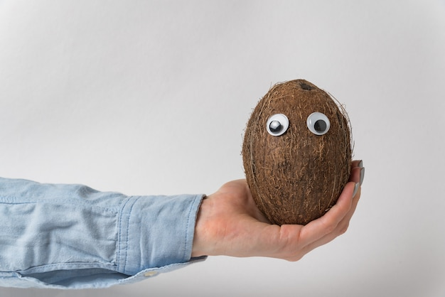 Hand holding brown coconut with googly eyes and funny face. white wall