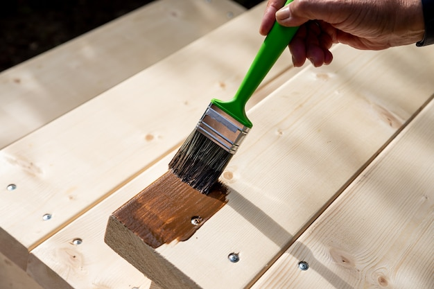 Hand holding a brush applying varnish paint on a wooden surface.