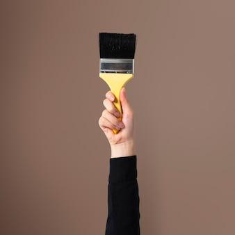 Рука держит кисть для росписи стен