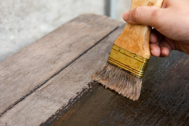 Hand holding a brush painting wooden timber boards surface with wood stain