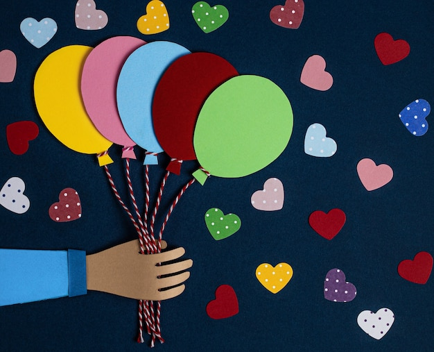Hand holding a bunch of colorful paper balloons