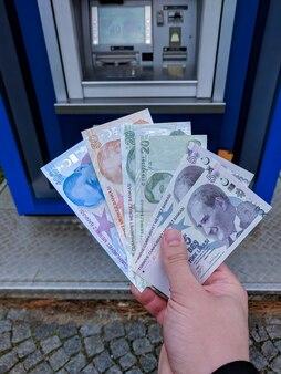 Рука держит кучу турецких лир возле банкомата