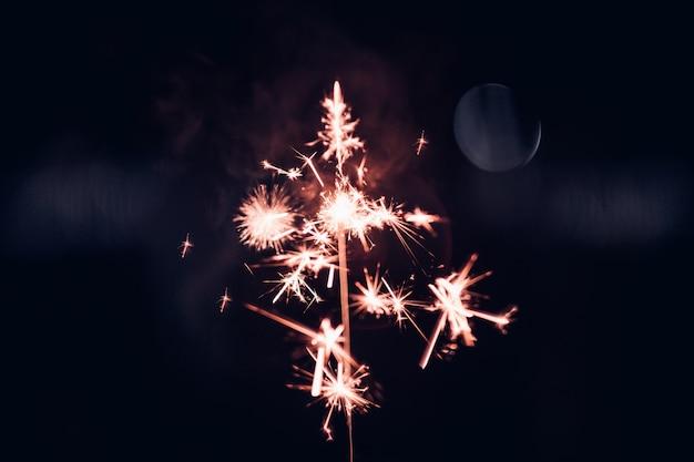 Hand holding burning sparkler blast on a black background at night