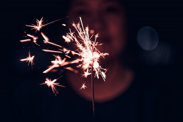 Hand holding burning sparkler blast on a black