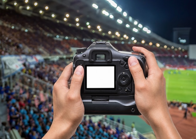 Hand holding the camera over abstract blurred photo crowd of spectators on a stadium