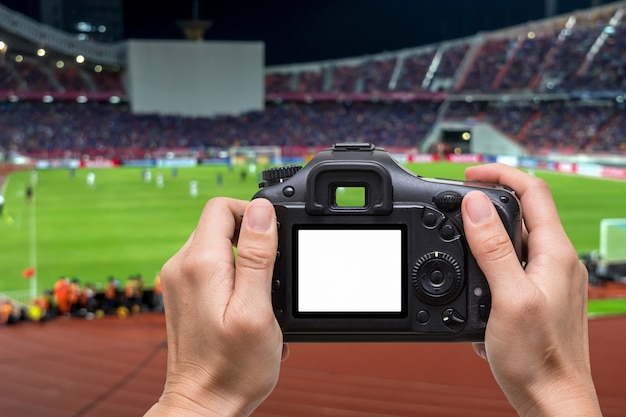 Hand holding the camera over blurred of action photographer taking photo at player