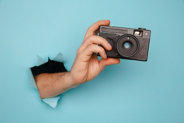 Hand holding camera from blue torn paper