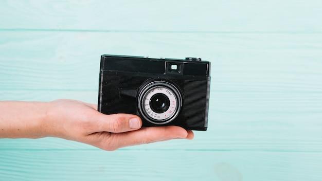 Macchina fotografica della holding della mano davanti a priorità bassa blu