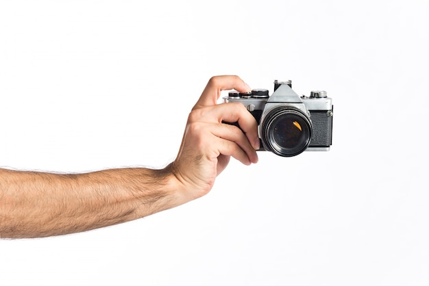 Hand holding a camera over white background