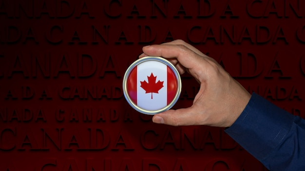 A hand holding a canada's national flag badge over dark red background