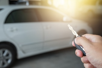 Hand holding car key remote at car park background