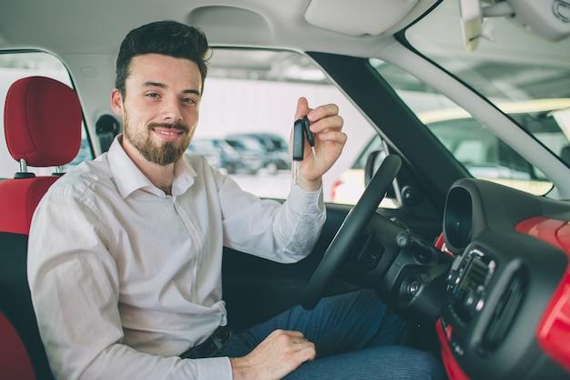 現代の車の背景を持つリモートの車のキーを持っている手。キーを持つ新しい車の中に座っている男。