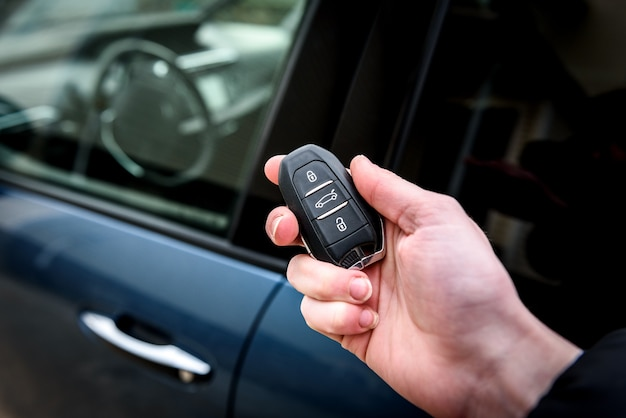 Hand holding a car key with remote control and pushing a button, he is unlocking the door.