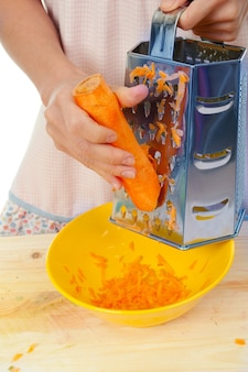 Hand holding carrot vegetable food kitchen grater .studio, white background.