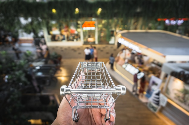A hand holding cart model with blur indoor shopping .