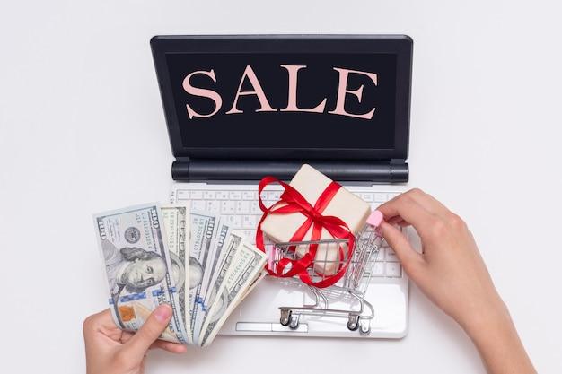 쇼핑 카트에 현금 달러와 선물을 들고 있는 손, 검은 화면에 sale라는 글자가 있는 노트북. 온라인 쇼핑 판매 개념입니다. 검은 금요일 개념입니다.