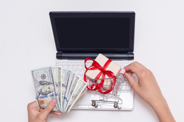 현금 달러, 빈 검은 화면이 있는 노트북, 쇼핑 카트에 선물을 들고 있는 손, 복사 공간. 온라인 쇼핑, 인터넷 상거래. 온라인 전자 상거래 쇼핑 인터페이스 개념입니다.