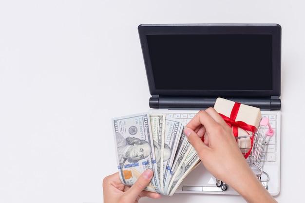 현금 달러, 빈 검은 화면이 있는 노트북, 쇼핑 카트에 선물을 들고 있는 손, 복사 공간. 온라인 쇼핑, 인터넷 상거래. 판매, 검은 금요일 개념입니다.