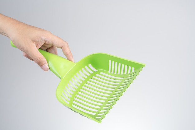 Hand holding cat or pet plastic litter tray scoop or waste scooper