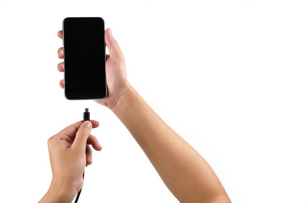 白い背景の上の充電器を接続する携帯電話を持っている手