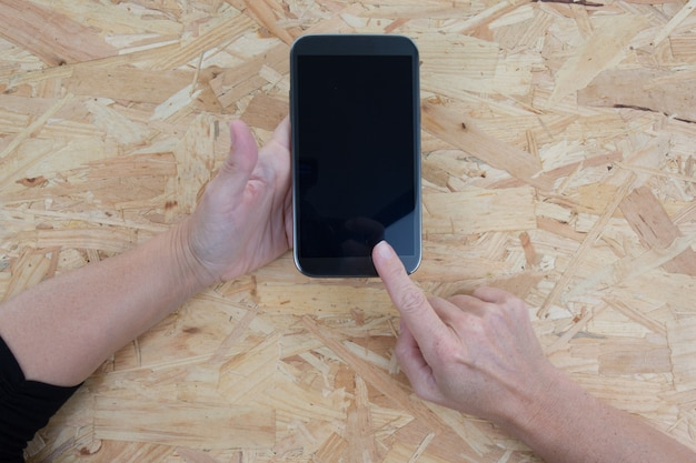 Рука держа сотовый телефон и касаясь экрана. изолированные