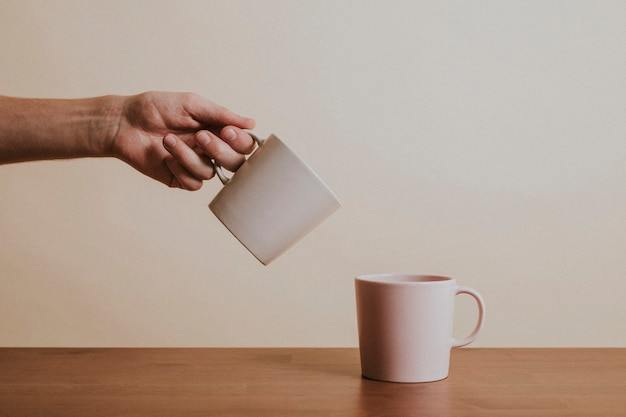 Hand holding a ceramic coffee cup