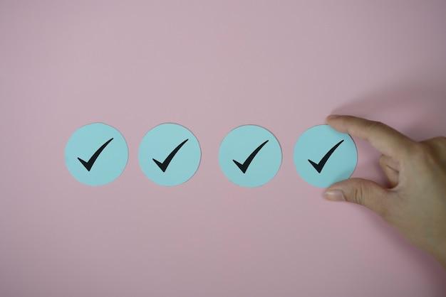 손을 잡고 확인 표시 아이콘 종이 분홍색 배경에 잘라