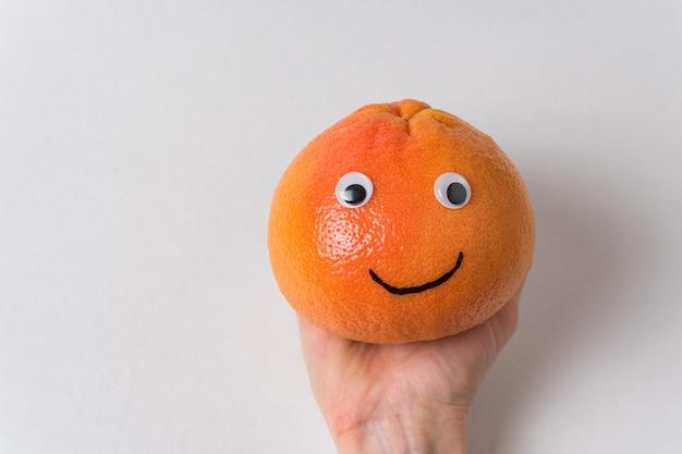 Рука веселый апельсин. оранжевый смайлик на белой стене. еда со смешными лицами.
