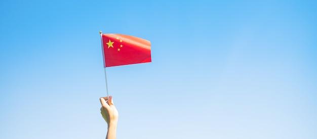 푸른 하늘 배경에 중국 국기를 들고 있는 손. 중화 인민 공화국의 국경일, 공휴일 및 행복한 축하 개념