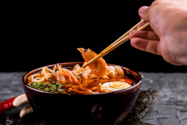 Hand holding chopsticks with shrimp ramen