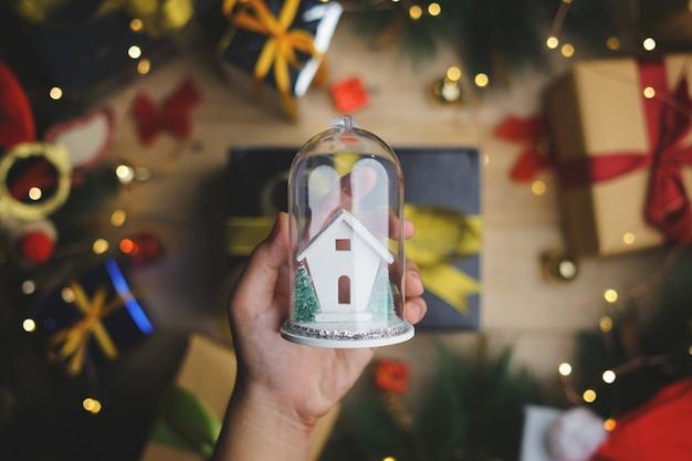 Hand holding christmas glass ornament above christmas decoration. top view