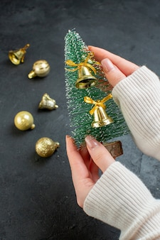 Hand holding christmas tree and decoration accessories on dark background