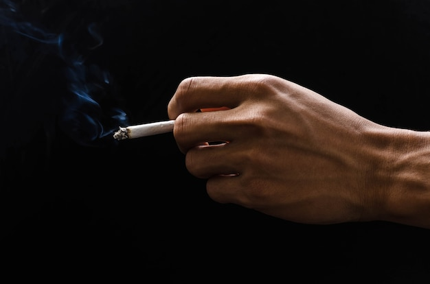 Hand holding cigarette and smoke on black