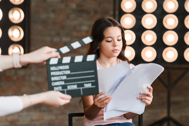 Hand holding clapper board in front of girl reading scripts in studio