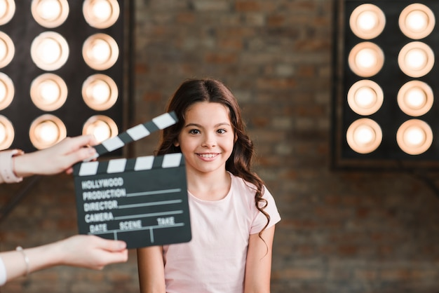 Hand holding clapper board in front of smiling girl