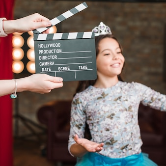Hand holding clapper board in front of girl performing in studio