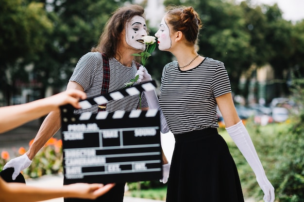 Hand holding clapperboard in front of loving mime couple