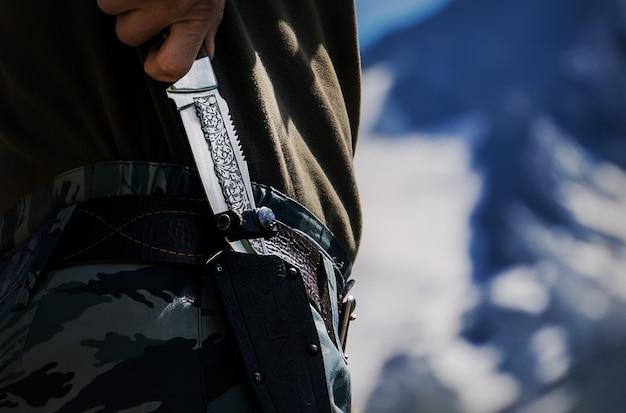 캠핑이나 하이킹을 좋아하는 사냥꾼을 위해 칼집이 있는 클래식 칼을 손에 들고 있습니다. 여행, 라이프스타일, 익스트림 익스플로러 장비. 위장복을 입은 군인. 칼집 근접 촬영에 칼