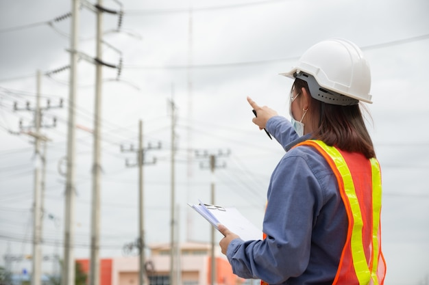 Hand holding clipboard and write on document checklist high voltage system, working woman