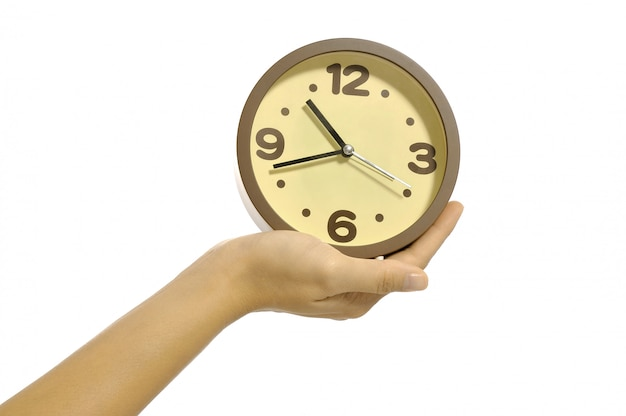 Hand holding clock isolated over white background. overtime concept