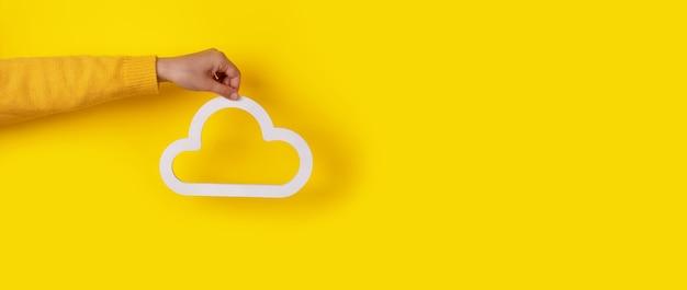 노란색 배경, 스토리지 개념 위에 구름 아이콘을 잡고 손