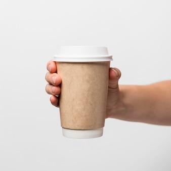Mano che tiene il primo piano della tazza di caffè