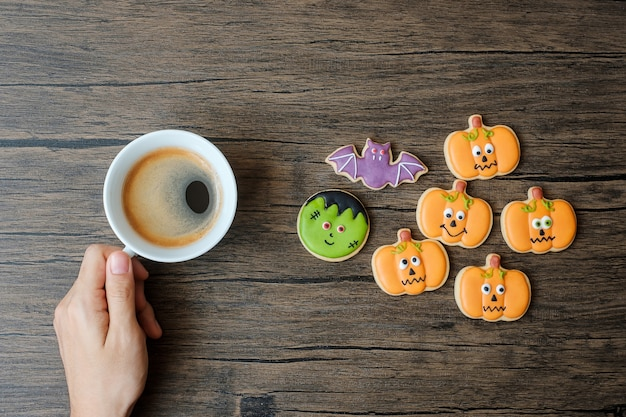 面白いハロウィーンのクッキーを食べている間、コーヒーカップを持っている手。幸せなハロウィーンの日、トリックまたは脅威、こんにちは10月、秋秋、伝統的な、パーティーや休日のコンセプト