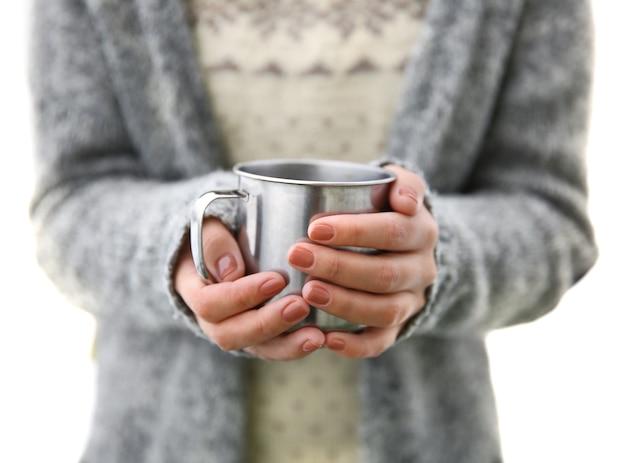 Рука держит чашку кофе, на открытом воздухе