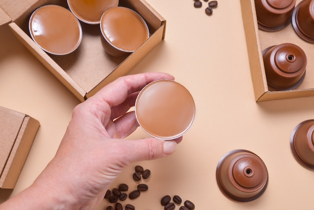 Hand holding coffee machine pods, capsules on beuge background