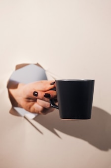 A hand holding a coffee mug through a torn paper background. copy space.