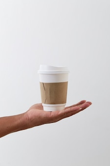 Hand holding a coffee paper cup isolated on light grey wall