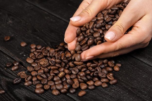 木製のテーブルにコーヒー豆とコーヒーを持っている手